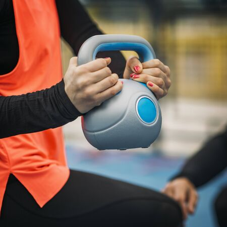 Young sporty woman lifting kettlebell, working with personal fitness trainer.