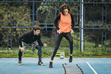 Young woman exercising with personal fitness coach using agility ladder. Agility skill improvement. Stock Photo