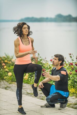 Exercising by the river with personal trainer