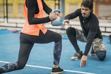 Personal fitness trainer working with young woman, doing kettlebell exercises, outdoors. Stok Fotoğraf