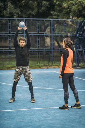 Fit and healthy personal trainer showing kettlebell exercise to a female client. Stok Fotoğraf