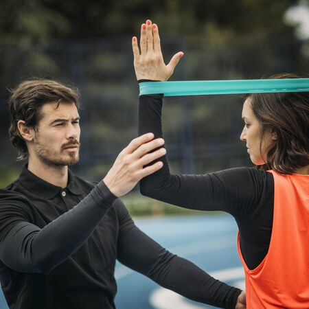 Personal fitness trainer coaching young woman, doing resistance band exercises.