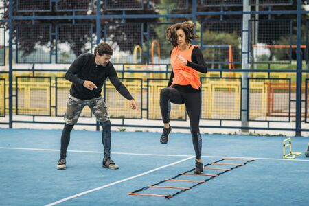 Young woman exercising with personal fitness coach using agility ladder. Agility skill improvement.