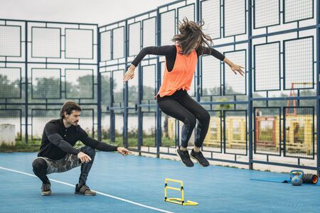 Hurdle jumping training outdoors.  Sporty woman jumping over the hurdle, fitness coach assistance.