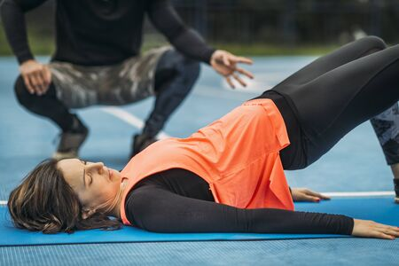 Young sporty woman exercising outdoors with personal fitness trainer