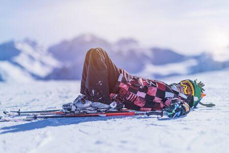 Boy lying on the snow, resting on top of ski resort.