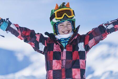 Smiling male child on top of ski resort enjoying winter.