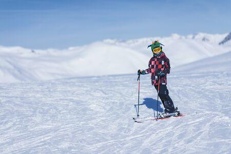 Jonge mannelijke skiër in kleurrijke outfit bovenop het skiresort in de bergen. Ruimte voor tekst kopiëren.