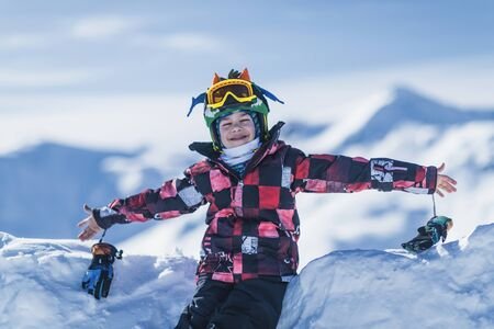 Child on top of ski resort enjoying with open arms.