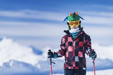 Young male skier in colorful outfit on top of mountain ski resort. Copy space for text.