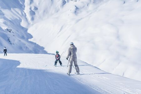 Mother and son skiing enjoying winter season on top of ski resort.