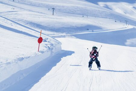 Child skiing in mountains. Active teenage kid with safety helmet, goggles and ski poles running down ski slope.  Snowy landscape, sunny day in winter season