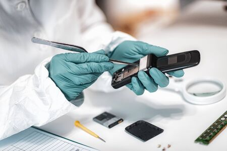 Digital Forensic Science. Police Forensic Analyst Examining Confiscated Mobile Phone. 스톡 콘텐츠