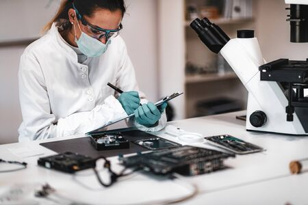 Forensic Science Technician Examining Computer Hard Drive.