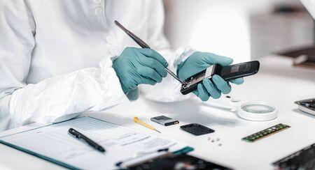 Ciencia forense digital. Analista forense de la policía examinando el teléfono móvil confiscado. Foto de archivo
