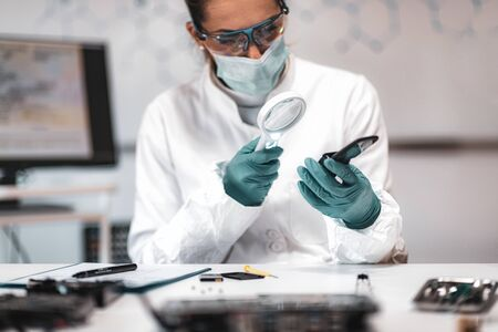 Digital Forensic Science. Police Forensic Analyst Examining Confiscated Mobile Phone. Stock Photo