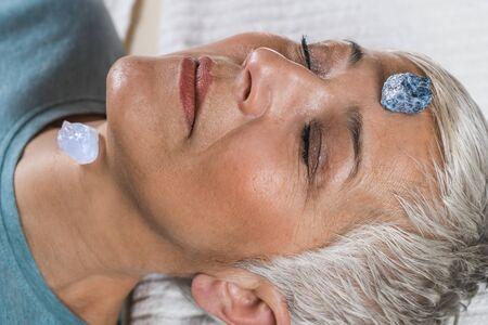 Healing and Balancing Chakras Therapy. Beautiful elderly woman lying on massage table and enjoying chakra healing treatment