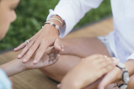 Female energy healer performing alternative therapy treatment with client. Therapist holding hands with patient, transferring energy. Imagens