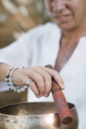 Woman playing on Tibetan singing bowl outdoors Фото со стока