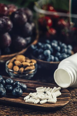 Trans-Pterostilbene supplements surrounded with antioxidant food. Blueberries, red grapes and almonds. Close up shot, focus on supplement.