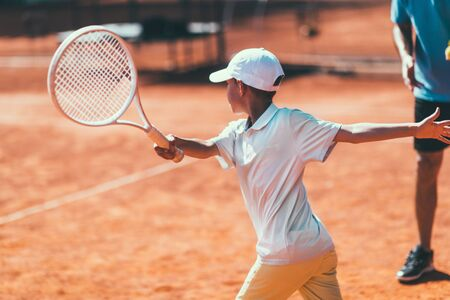 Tennis Instructor with Young Talent on Clay Court. Boy having a Tennis Lesson. Imagens