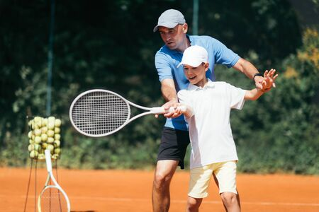 Boy Training with Tennis Instructor on a Clay Court