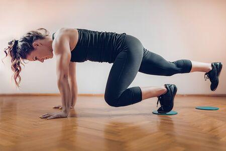 Female Athlete Exercising with Sliding Discs.