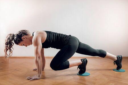 Sportswoman exercising, using Gliding Discs. Imagens