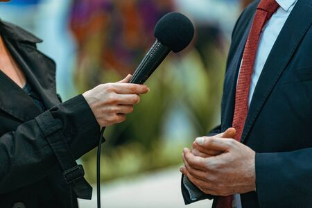 Giornalisti che tengono microfono e dittafono, intervistando l'altoparlante dell'uomo d'affari. Archivio Fotografico