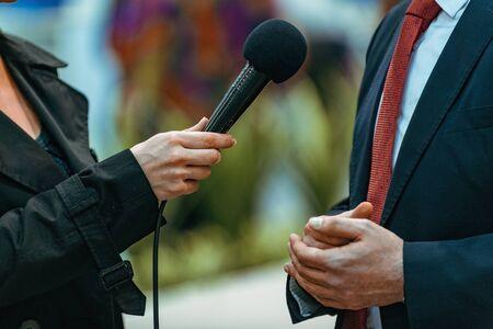 Periodistas con micrófono y dictáfono, entrevistando al orador del empresario. Foto de archivo
