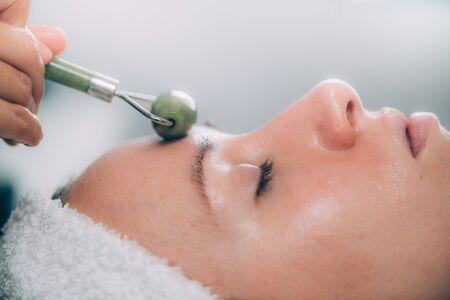 Cosmetologist using jade stone roller for Guasha face drainage massage