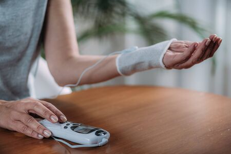 Senior Woman Doing Wrist Joint Physical Therapy with Conductive TENS Electrode Sock, Transcutaneous Electrical Nerve Stimulation