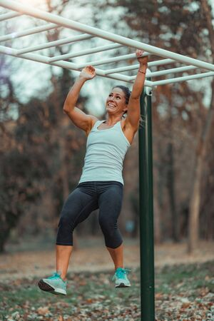 Attractive Woman Exercising on Monkey Bar in the Park. Reklamní fotografie