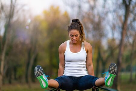 Woman Exercising on Parallel Bars in the Park. Reklamní fotografie