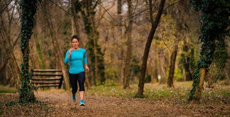 Female Athlete Jogging in Park. Autumn, Nature Reklamní fotografie - 140367515