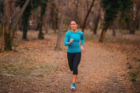 Female Athlete Jogging in Park. Autumn, Nature Reklamní fotografie - 140368117