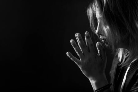 Anxiety mental disorder – portrait of a troubled woman on black background