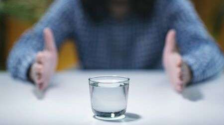 Telekinesis – Young man trying to develop telekinetic powers, practicing with glass of water Stock Photo