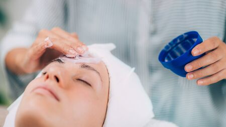 Applying face calming mask on beautiful woman's face. Shaken protein mousse. Stock Photo