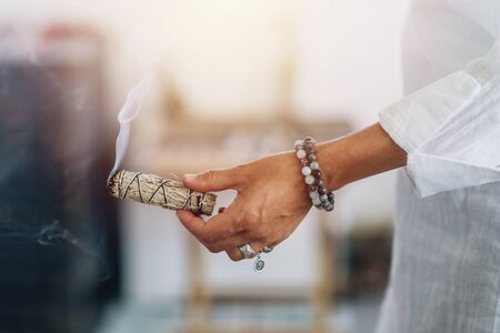 Smudging - Hands of a spiritual woman holding burning smoking sage smudge stick Imagens