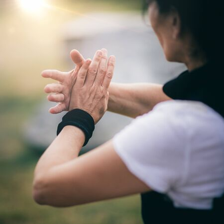 Qi Gong training outdoors, woman's hands in focus.