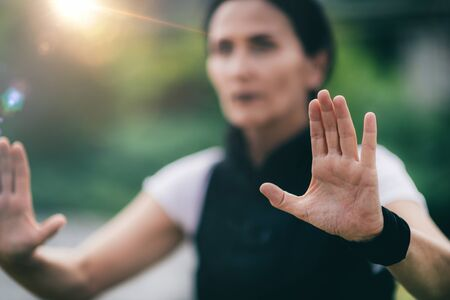 Qi Gong. Mature woman practicing Qi Gong in a park. Focus on woman's hands.