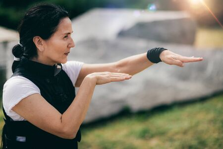 Qi Gong practice. Mature woman exercising Qi Gong in a park.