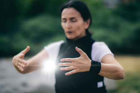 Chi Gong energy practice. Mature woman exercising in a park.