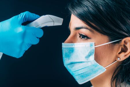 Coronavirus. Medizinischer Arbeiter in Hazmat-Schutzsuite, der die Körpertemperatur überprüft, Frau mit Schutzmaske