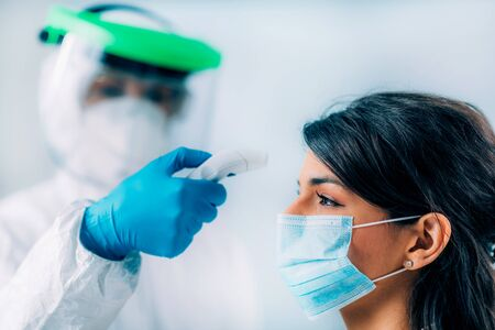 Coronavirus Screening. Medical worker in protective suit measuring body temperature with contactless body thermometer, young woman wearing protective mask
