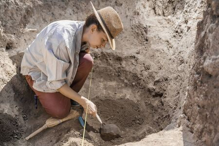 Archaeologist digging with hand trowel, recovering ancient pottery object from an archaeological site.