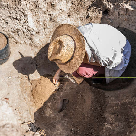 Archaeologist digging with hand trowel, recovering ancient pottery object from an archaeological site. Banque d'images - 150819571