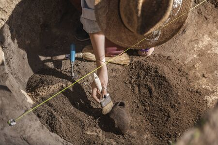 Female archaeologist digging up ancient pottery object at an archaeological site.