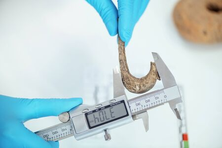 Young archaeologist measuring ancient hook with digital caliper. Archivio Fotografico